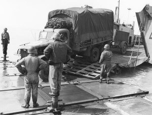 Seabees watch trucks roll onto an Rhino ferry in Normandy